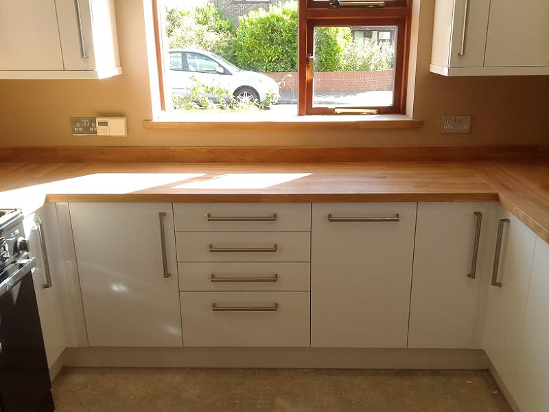 Logica white gloss kitchen fitted with oak worktops for Oak fitted kitchen